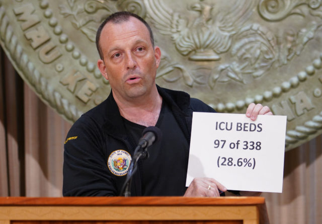 Lt Governor Josh Green holds placard 'ICU Beds 97 of 338 (28.6%) during Coronavirus COVID-19 press conference held at the Capitol. April 8, 2020.