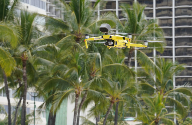 Honolulu Fire Department drone flies over Waikiki Beach notifying people on beach with a small speaker. April 10, 2020.
