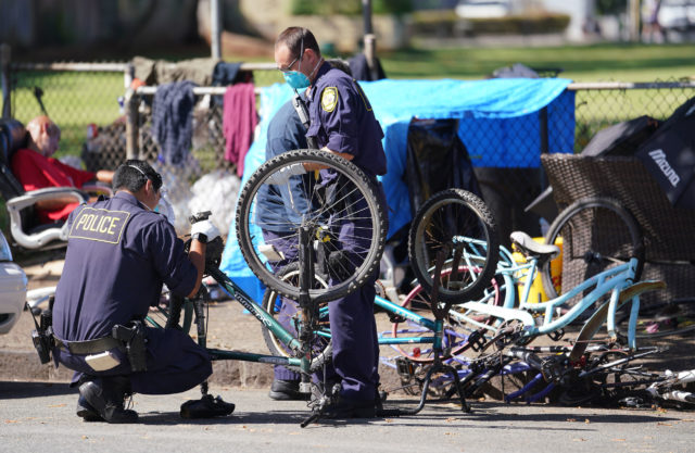 HPD officers confiscate bicycles from encampment near Moiliili Field during Coronavirus pandemic. April 17, 2020.