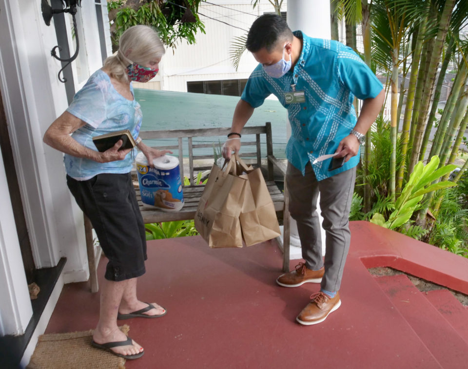 "Carol Wood recieves a grocery delivery by ""Our Ohana"" volunteer John Hulihe'e on Thursday, April 23, 2020.  The program connects Kupuna with local sponsors who are COVID-19 free and willing to donate their time to pick up groceries, medication, and needed supplies for Kupuna so they don't have to leave their homes until the stay home orders are lifted. (Ronen Zilberman photo Civil Beat)"