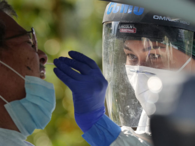 A volunteer from the the COVID Command Mobile Unit, led by Dr. Scott Miscovich, swabs the nose of a Hawaii resident who showed up for the free drive through testing event in Wahiwa,HI on Wednesday, April 22, 2020. (Ronen Zilberman photo Civil Beat)