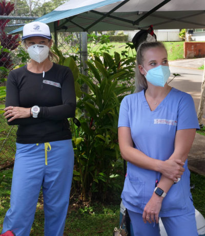 Unpaid volunteers Chris Tomlinson, a Honolulu hospital nurse (left) and Stephany Hall, a nurse (right) wait for people to arrive so they can start the screening process for COVID-19 testing during the free drive through event in Wahaiwa, HI, on Wednesday, April 22, 2020. (Ronen Zilberman photo Civil Beat)