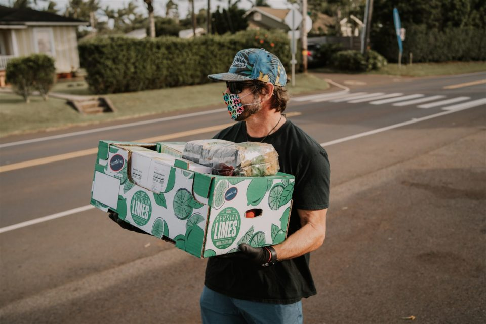 Campbell Farrell of Love the Sea on Maui carries a box of donations to eh food bank set up at the Kuau store.