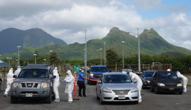 Volunteers from the the COVID Command Mobile Unit, of the Premier Medical Group Hawaii, screen and and perform nose swab tests on Waimanalo residents who came for the free drive through testing event on Sunday, April 26, 2020. (Ronen Zilberman photo Civil Beat)