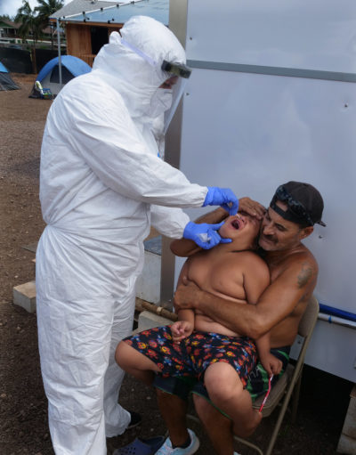A volunteer from the the COVID Command Mobile Unit, of the Premier Medical Group Hawaii, performs a swab test on Hui Mahi'ai Aina resident, Luke Mossman 7yrs. old while his dad, Dylan Spencer, holds him still on his lap, Sunday, April 26, 2020. (Ronen Zilberman photo Civil Beat)