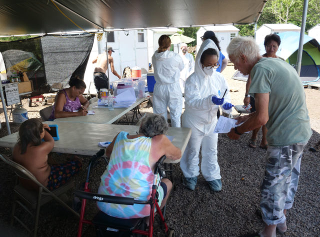 Volunteers from the the COVID Command Mobile Unit, of the Premier Medical Group Hawaii, have residents from Hui Mahi'ai Aina community fill-out forms so they can recieve free COVID-19 nose swab tests in Waimanalo, HI, on Sunday, April 26, 2020. (Ronen Zilberman photo Civil Beat)