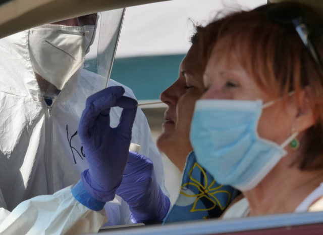 A volunteer from the the COVID Command Mobile Unit, of the Premier Medical Group Hawaii, performs a nose swab test for Waimanalo residents that came to the free drive through testing event Sunday, April 26, 2020. (Ronen Zilberman photo Civil Beat)