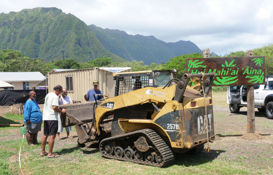 Volunteers and community members from Hui Mahi'ai 'Aina work together to build a foundation for a new structure at the Hui Mahi'ai 'Aina camp in Waimanalo, HI, on Sunday, April 26, 2020. (Ronen Zilberman photo Civil Beat)