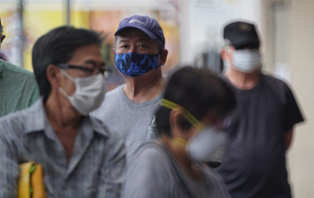Masked and standing in line waiting to get into Longs Drugs in Moiliili during COVID-19 pandemic. April 28, 2020