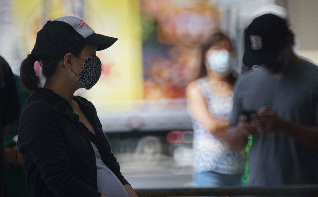 Silhouetted Longs Drugs customers as they wait socially distanced and wearing masks during COVID-19 pandemic. April 28, 2020