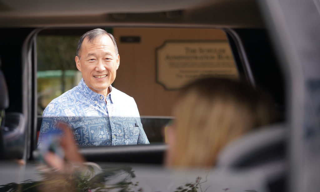 Le Jardin Principal Earl Kim speaks thru car window to kids as parents drive to school to pickup packets.
