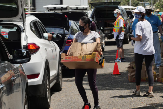 A volunteer loads a box of groceries into the trunk of a car at the big food distribution event held at Aloha Stadium in Honolulu, HI, Wednesday, May 6, 2020. The city of Honolulu, Hawaii Foodbank, and Hawaii Community Foundation collaborated to put on the event providing food for approximately 4,000 Oahu households. (Ronen Zilberman photo Civil Beat)
