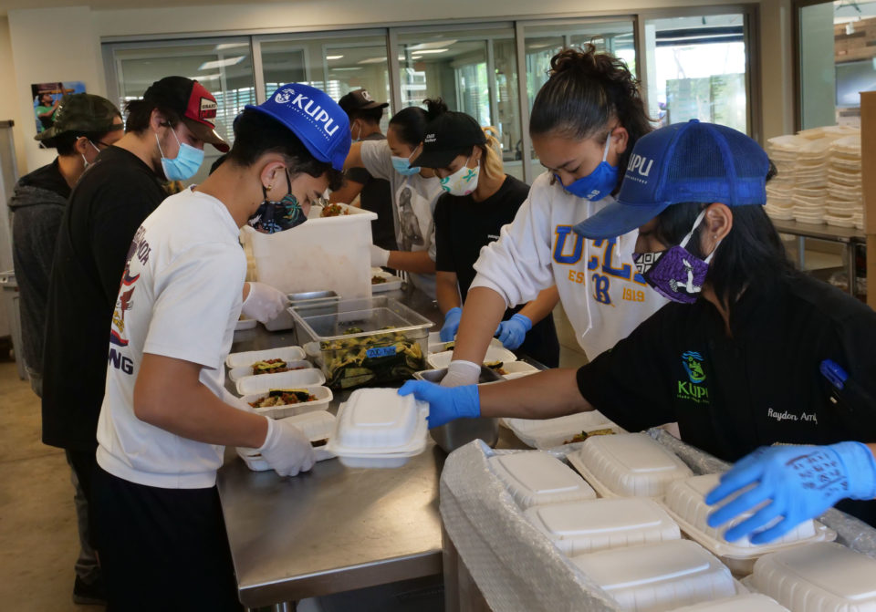 From left to right: Orion Fonoti, Kainoa Reyes, Adrian Salvador, Jacenda Fonoti, and Raydon Amba, of the Kupu non-profit organization, finish preparing and packing meals into boxes to be sent out to hard hit areas of Oahu due to the COVID-19 pandemic, on Wednesday, May 13, 2020, in Honolulu, HI. The group is part of the Kupu culinary program, founded as a social enterprise that provides opportunities for youth  to train in career paths like kitchen management and food preparation. Kupu currently prepares 1200 meals a day for island communities in Waimanalo, Kahaluu, Hau'ula, and Waianae. (Ronen Zilberman photo Civil Beat)