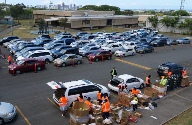 Volunteers from the Lighthouse Outreach Center give out food to Kalihi community members during a distribution event on Thursday, May 14, 2020. Cars snaked for blocks as hundreds of people showed up to receive food donations. (Ronen Zilberman photo Civil Beat)