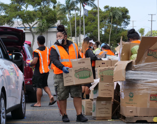 Volunteers from the Lighthouse Outreach Center load boxes of food into the cars of Kalihi community members during a distribution event on Thursday, May 14, 2020. Cars snaked for blocks as hundreds of people showed up to receive food donations. (Ronen Zilberman photo Civil Beat)