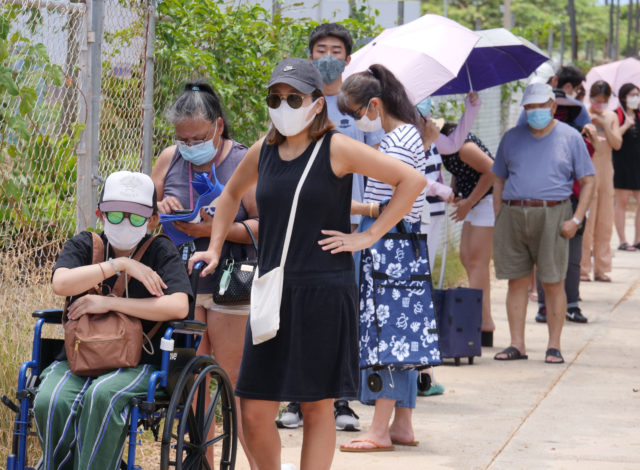 Local residents stand in line to receive food at a distribution event held at the Na Kupuna Makamae Center, in Honolulu, HI, Friday, May 15, 2020. The center normally runs programs and services for seniors and since the COVID outbreak has become home for a weekly food distribution project made available by a partnership between the Pacific Gateway Center, Aloha Harvest, and Help is on the Way organizations. (Ronen Zilberman photo Civil Beat)
