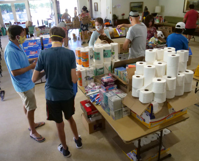 Volunteers sort grocery donations from a food drive at the Central Union Church, in Honolulu, HI, Saturday, May 16, 2020. The Central Union Church partnered up with nonprofit corporatio, Help is on the Way, to collect and deliver food boxes to kupuna and other vulnerable, homebound people on Oahu. They hope to create 200 grocery boxes that will be delivered in the coming week. (Ronen Zilberman photo Civil Beat)