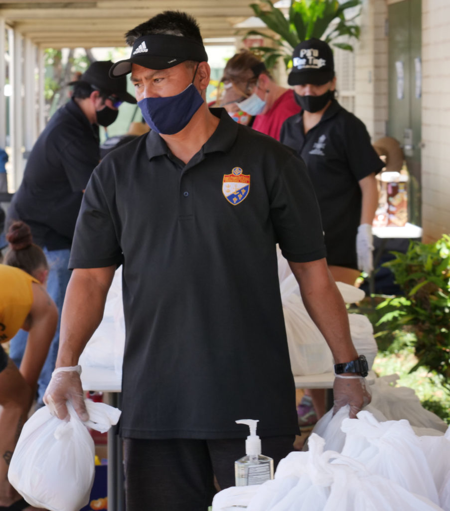Volunteers from the Lodge Le Progres De L'Oceanie of the Free & Accepted Masons of Hawaii, prepare bags, of free groceries, to be given out to community members in need, at the drive through distribution event they held, at Kaimuki High School on Sunday, May 17, 2020, in Honolulu, HI. (Ronen Zilberman photo Civil Beat)