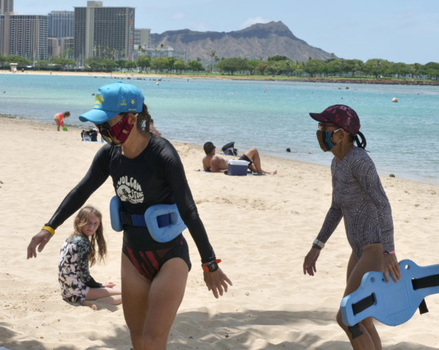 Judith Inazu (left) and Lorie Young (right) head to the showers, after finishing their aqua jogging class in the water, at Ala Moana Beach Park, Thursday, May 28, 2020, in Honolulu, HI. The ladies are some of the very few beach goes who choose to keep their masks on even while in the water. (Ronen Zilberman photo Civil Beat)