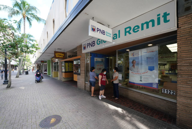 Customers wait outside PNB Global Remittance located on Fort Street Mall.
