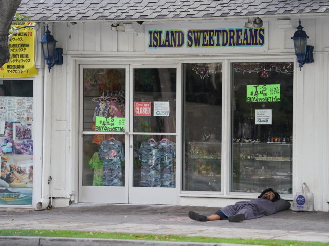 Man sleeps under awning fronting Island Sweetdreams located on Kuhio Avenue, Waikiki with very little foot traffic during COVID-19 pandemic. June 1, 2020