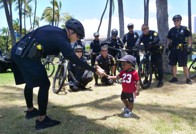 Jonah Hosa (2 yrs. old from Honolulu) recieves a card from Officer T. Cagulada of the Honolulu Police Department, before the start of a Black Lives Matter rally at Ala Moana Beach Park, Friday, June 5, 2020. Hundreds of people showed up for the walk from Magic Island to the Duke statue in Waikiki to raise awareness against police brutality and racism across the nation. (Ronen Zilberman photo Civil Beat)