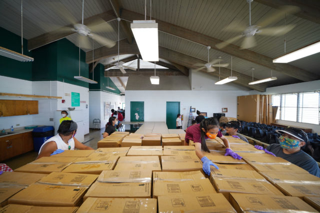 Volunteers stack boxes of food at Papakolea Community Center to be distributed shortly to community members during COVID-19 pandemic.