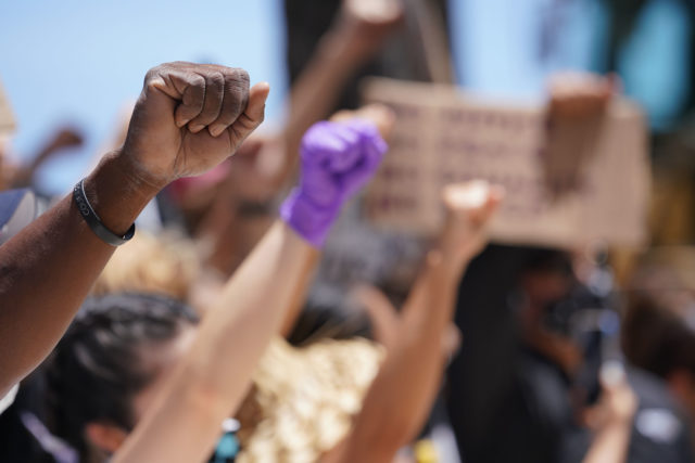 Black Lives Matter Peaceful Protest supporters raise their hands in a fist at the Duke Kahanamoku Statue after marching from Ala Moana Beach Park.