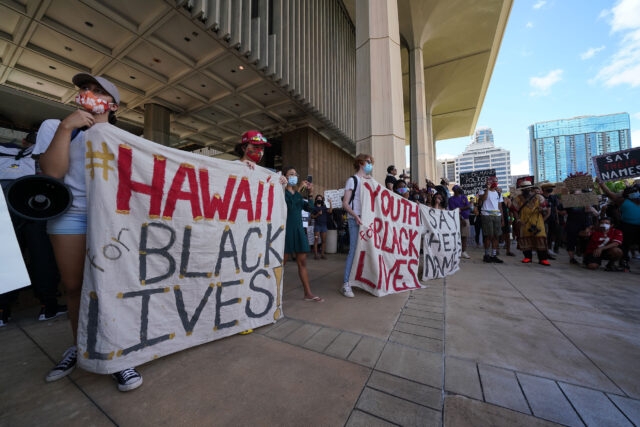 Black Lives Matter supporters holds banners at the Capitol.