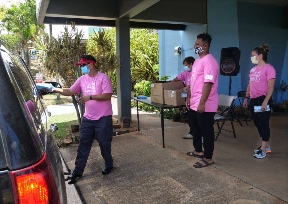 Dr. Jason Hughes, Chief Medical Officer of Kahuku Medical Center, (left) hands out free PPE masks to community members during a drive through event at the Kahuku Medical Center, Saturday, June 6, 2020. The masks were made available to North Shore residents through the Every1ne For One Hawaii organization as a follow-up to their May 2nd drive, where over 8,000 face masks were given out in only two hours. (Ronen Zilberman photo Civil Beat)