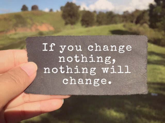 If You Change Nothing, Nothing Will Change written on a paper. Blurred vintage styled background.