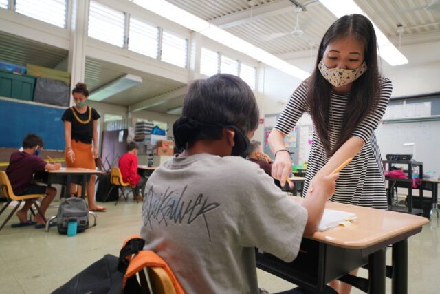 Kaneohe Elementary School summer school teacher Jacque Yoshizumia helps a student during COVID-19 pandemic. June 12, 2020