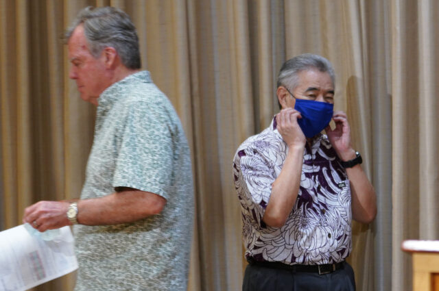 Governor David Ige walks toward podium as Dr Bruce Anderson heads back to sit down during press conference held during COVID-19 pandemic. June 15, 2020
