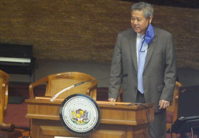 House Speaker Scott Saiki stands at podium with mask dangling on his ear before session begins during COVID-19 pandemic. June 22, 2020