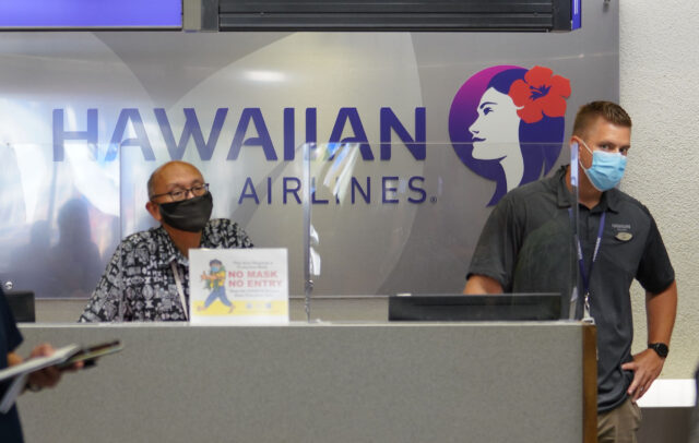 Hawaiian Airlines COVID19 safety gear Interisland terminal as workers watch press conference announcing that Hawaii travelers that are negative COVID-19 pretest are allowed not to quarantine. June 24, 2020