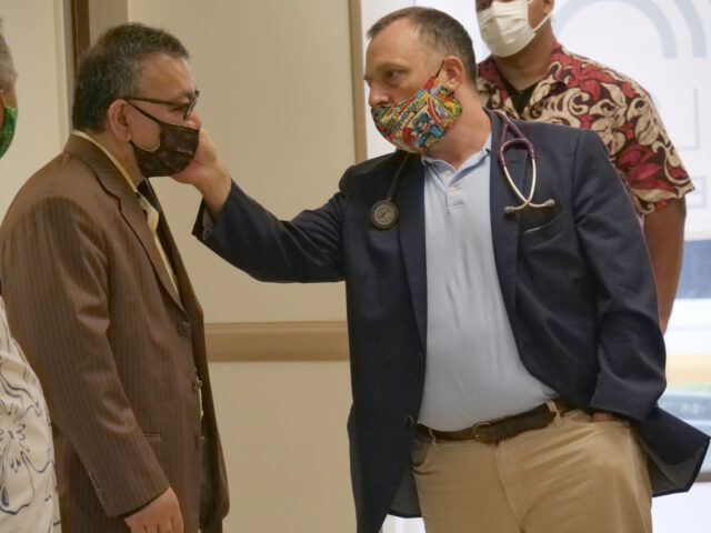 Lieutenant Governor Dr. Josh Green helps John Mizuno adjust his face mask at the Aloha Free Clinic in Honolulu on Thursday July 2, 2020. The Hawaii Dental Association Foundation donated 2,500 kits which included toothpaste, toothbrushes, floss, and educational materials to the Aloha Free Clinic. (Photo: Ronen Zilberman/Civil Beat)