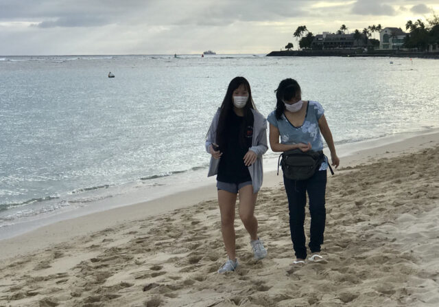 Beach goers at Ala Moana Beach Park wear masks as a COVID precaution in Honolulu, HI. (Ronen Zilberman photo Civil Beat)