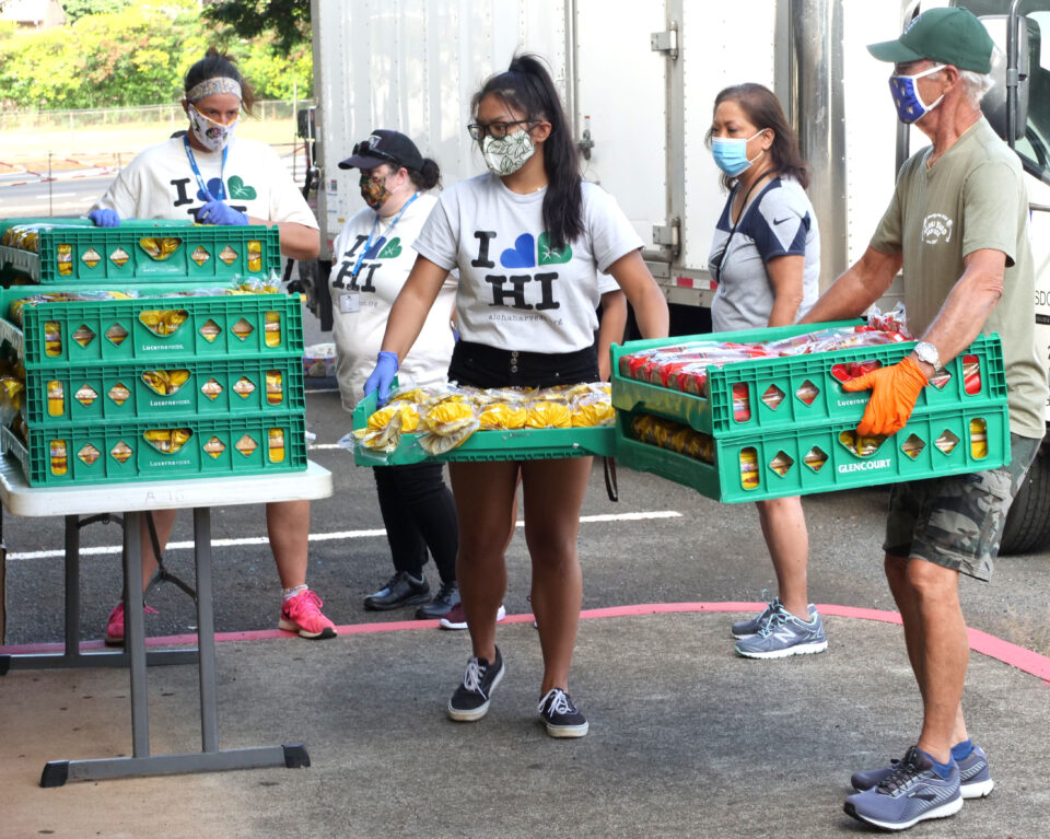 Volunteers organize bins of bread to be given out during a food distribution event held at Aiea High School on Friday, July 10, 2020. The HLTA (Hawaii Lodging & Tourism Association) and Aloha Harvest collaborated with the City of Honolulu to put on the event. (Ronen Zilberman photo Civil Beat)