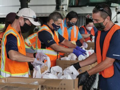 Volunteers assemble food boxes for a distribution event at Windward Community College on Saturday, July 11, 2020. The event was a collaboration between 14 contractors & developers, The Great Aloha Run, and the Hawaii Foodbank spcecifically designed to serve residents of the Windward side from Kualoa to Waimanalo. (Ronen Zilberman photo Civil Beat)