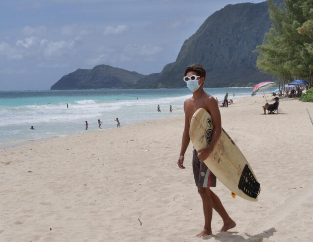 Koa Yokota arrives to the beach with his short board and COVID mask to catch some waves in Waimanalo, HI, on Sunday, July 12, 2020. (Ronen Zilberman photo Civil Beat)