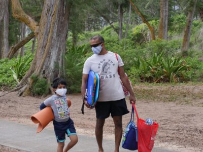 On the Windward side of Oahu, Suketu Naik and his son Agam Keral head to the beach with their protective masks in Waimanalo, HI, Sunday, July 12, 2020. (Ronen Zilberman photo Civil Beat)
