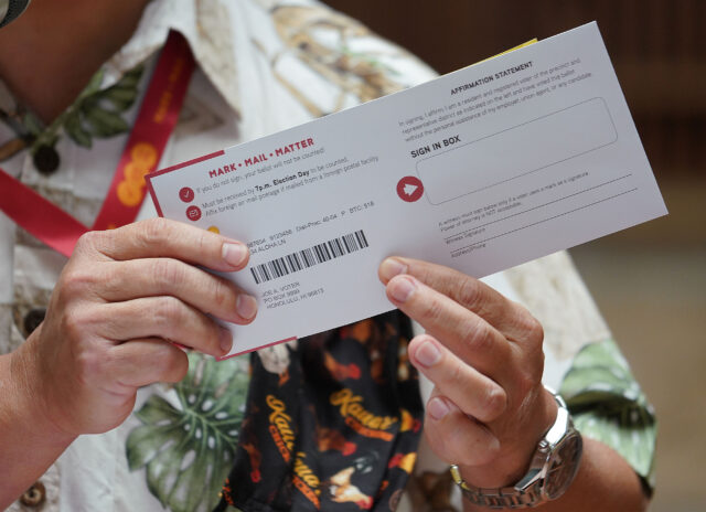 Honolulu City Clerk Glen Takahashi holds a sample of a Mail in ballot during press conference held at Honolulu Hale.