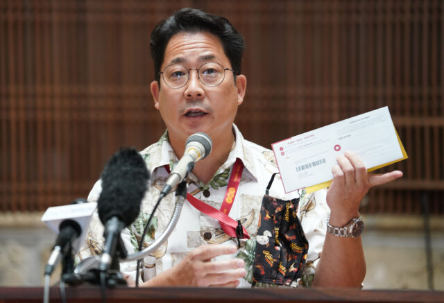Honolulu City Clerk Glen Takahashi holds a 'mail in ballot' during press conference held at Honolulu Hale.