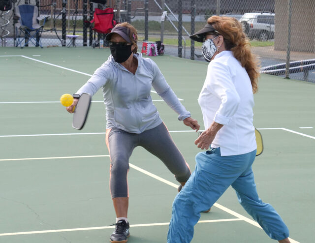 Aina Haina residents enjoy a game of pickleball with protective masks at Waialae Iki Park in Aina Haina, HI, Tuesday, July 15, 2020. Invented in 1965 in Washington State, pickleball can be played on a traditional tennis court with smooth paddles and a plastic hole-filled ball. (Ronen Zilberman photo Civil Beat)