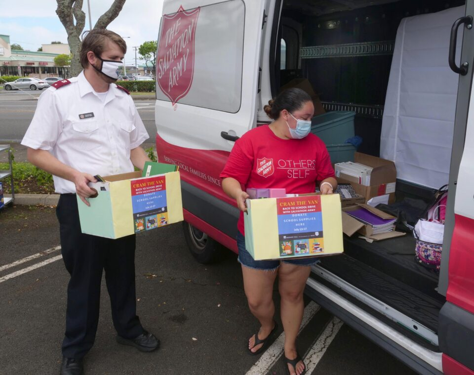 "Lt. Aaron Ruff, Core Officer (left) and Marissa Fierro, Volunteer Coordinator (right) both of the Salvation Army, load boxes of donations into their vehicle during their ""Cram the Van"" Back-to-School-Drive at the Windward Mall in Kaneohe, Saturday, July 18, 2020. This marks the second year in a row that the Windward Mall has partnered with the Salvation Army to help procure school supplies for the windward community. (Ronen Zilberman photo Civil Beat)"