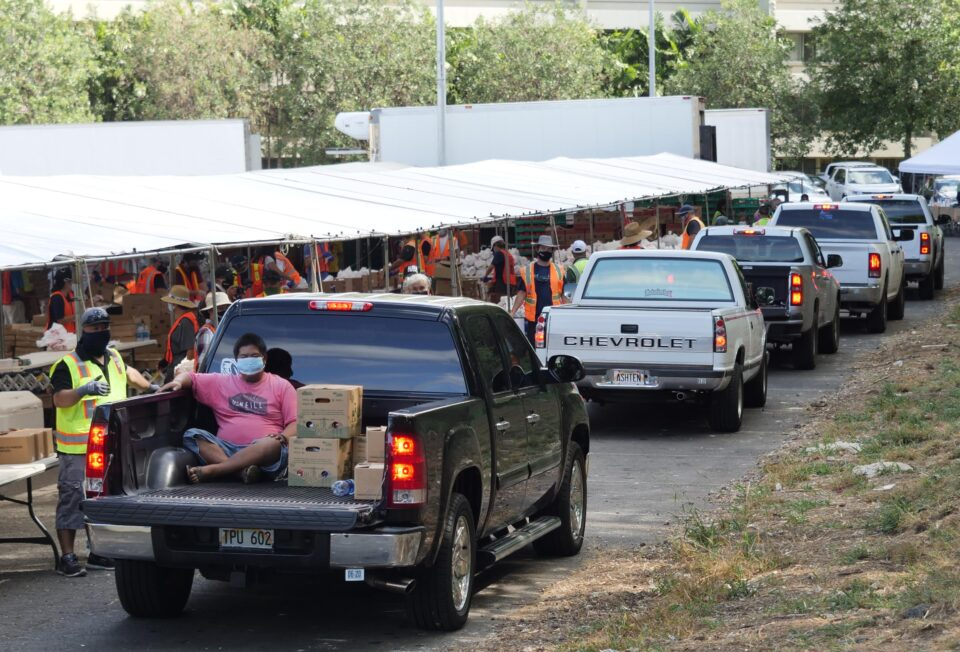 Trucks line up to recieve food donations from volunteers during a drive-thru event organized by the City and Hawaii Foodbank in Waianae, HI, Saturday, July 18, 2020. (Ronen Zilberman photo Civil Beat)