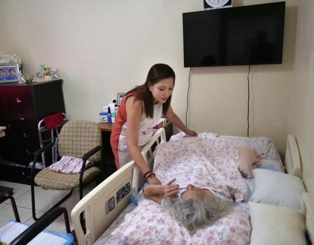 Maribel Tan visits with Annie Lum, one of the patients in her care home in Waipahu, HI, Monday, July 20, 2020. Maribel is the president of the Adult Foster Homecare Association of Hawaii. (Ronen Zilberman photo Civil Beat)