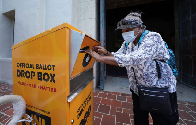 Kakaako resident Saidah Hatchett places her vote by mail envelope/ballot into a official ballot drop box located at Honolulu Hale. July 22, 2020.