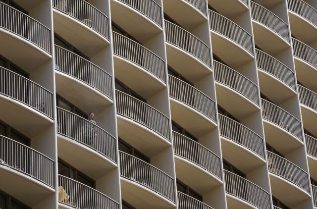 A visitor stands on the balcony of the Embassy Suites in Waikiki during COVID-19 pandemic. July 23, 2020