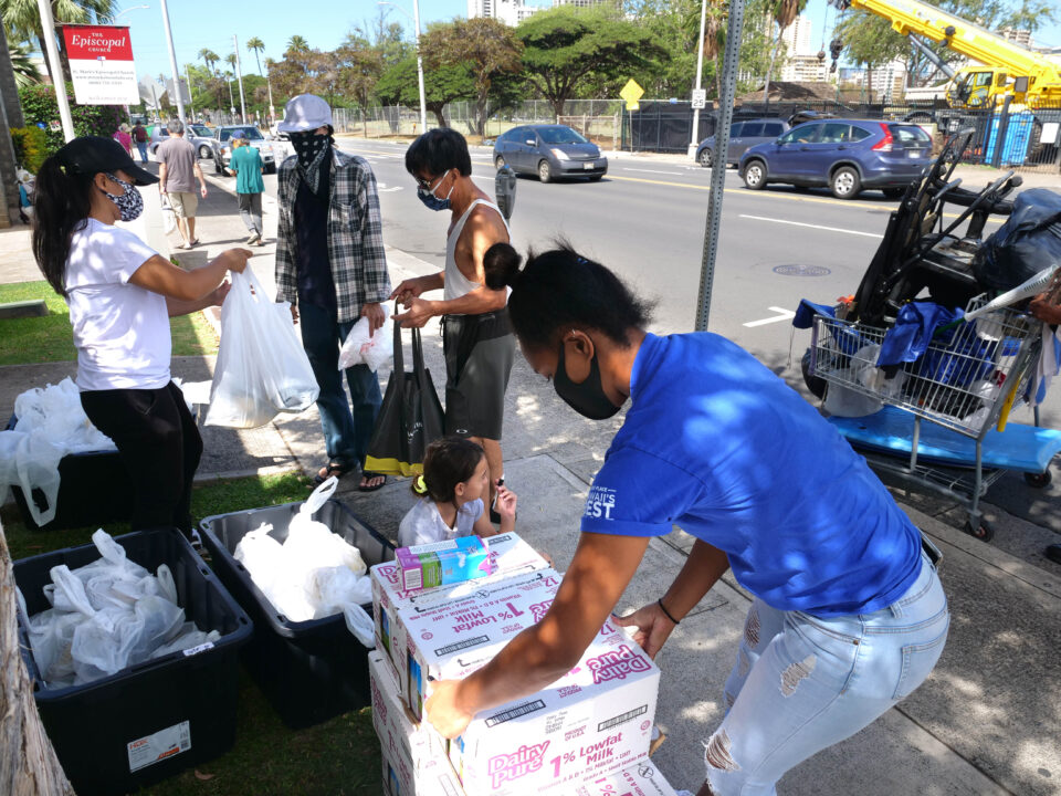 Kama'aina Kids volunteers Sisi Tuipulotu (right) and Rose Solis (left) pass out food donations to those in need, in partnership with St. Marks Episcopal Church, on Kapahulu St. in Kaimuki on Wednesday, July 29, 2020. (Ronen Zilberman photo Civil Beat)